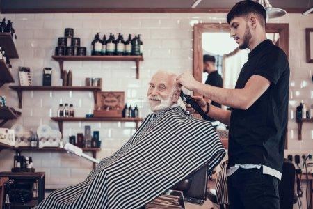 Hairdresser making haircut by hair