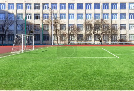 Soccer football field near urban school building