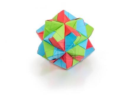 Photo pour Figure géométrique - dodécaèdre, une des espèces de polyèdres, faite par la méthode d'origami modulaire avec papier de couleur sur une surface mate sur fond blanc - image libre de droit