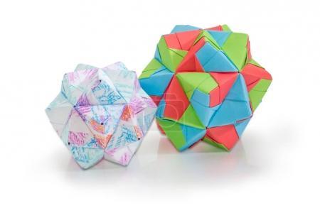 Photo pour Deux tailles de dodécaèdres - trois dimensions géométriques figure une des espèces de polyèdres, faites par la méthode d'origami modulaire avec divers document sur fond blanc - image libre de droit