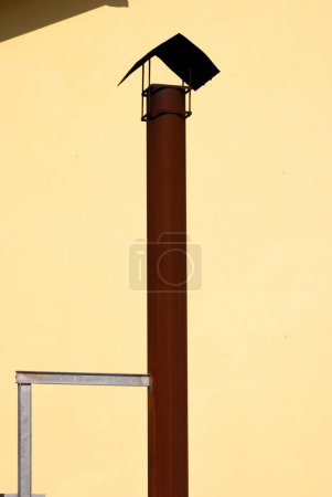 Metal flue and yellow wall