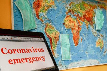 Photo pour Coronavirus Mots d'urgence sur une vidéo d'ordinateur portable et carte géographique du monde avec trois masques chirurgicaux accrochés dessus - image libre de droit