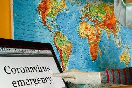 Photo pour Fille habillée avec des gants en latex et masque chirurgical pointant sur un ordinateur portable d'urgence Coronavirus mots avec le monde géographique comme arrière-plan - image libre de droit