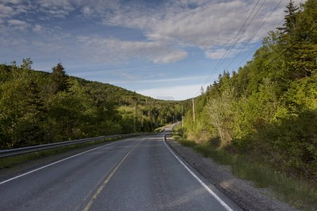Empty road amidst trees by hills, Ceilidh Trail, Cape Breton Island, Nova Scotia, Canada