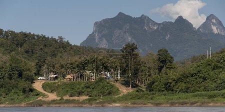 Shoreline village with rocky mountains in background, River Mekong, Pak Ou District, Luang Prabang, Laos