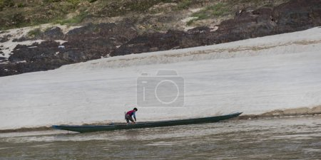 Person along side a row boat in River Mekong, Laos