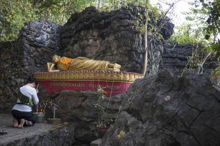 Woman praying at Reclining Buddha, Mount Phousi, Luang Prabang, Laos