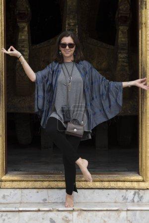 Woman standing at temple, Wat Xieng Thong, Luang Prabang, Laos