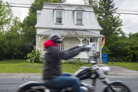 Man riding motorcycle on road by house, Doaktown, New Brunswick, Canada