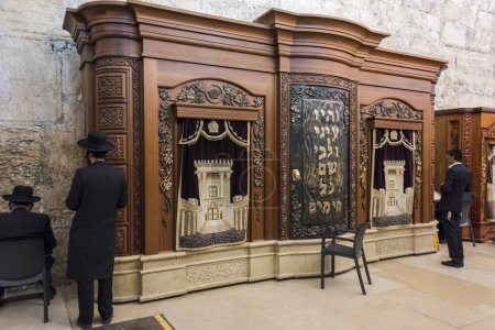 Jewish men praying near wooden cabinet with Torah scrolls in Cave Synagogue adjoining Western Wall, Old City, Jerusalem, Israel