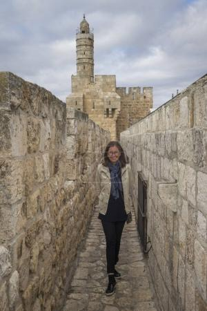 Happy woman standing in wall promenade in the old city with Tower of David in background, Jerusalem, Israel