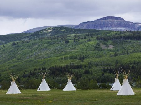 Teepees on landscape with mountain range in the background, Glacier National Park, Glacier County, Montana, USA
