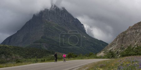 Two people riding bicycles on road, Many Glacier, Glacier National Park, Glacier County, Montana, USA