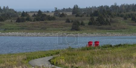 Scenic view of adirondack chairs at riverbank, Louisbourg Harbour, Cape Breton Island, Nova Scotia, Canada