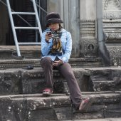 Woman looking at her cell phone at Hindu temple in Angkor Wat, Banteay Samre, Siem Reap, Cambodia