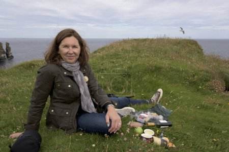 Happy woman relaxing at coast, Duncansby Head, John o' Groats, Caithness, Scottish Highlands, Scotland