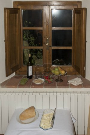 Photo for Various food and bottle of wine on windowsill near wooden window - Royalty Free Image