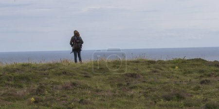 Rear view of a woman standing at coast, Duncansby Head, John o' Groats, Caithness, Scottish Highlands, Scotland