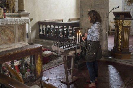 Photo pour Bougies allumantes pour femme dans l'église, Chianti, Toscane, Italie - image libre de droit