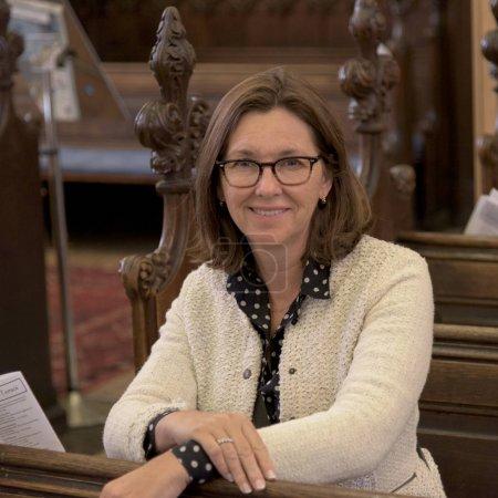 Portrait of happy woman sitting in a pew at Church of St John the Evangelist, Edinburgh, Scotland