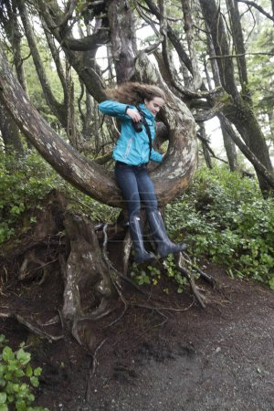 Girl jumping from tree, Wild Pacific Trail, Ucluelet, Pacific Rim National Park Reserve, Vancouver Island, British Columbia, Canada