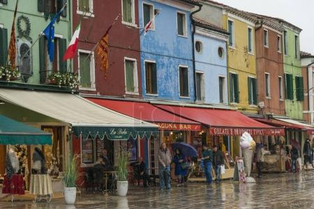 People outside of stores by wet street during rain, Burano, Venice, Veneto, Italy