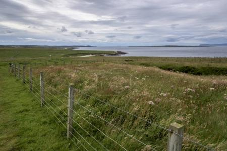 Fence at coast against cloudy sky, John o' Groats, Caithness, Scottish Highlands, Scotland
