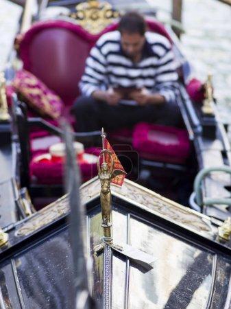 Man on gondola in canal, Venice, Veneto, Italy