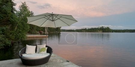 Outdoor chair and umbrella on dock, Lake of The Woods, Ontario, Canada