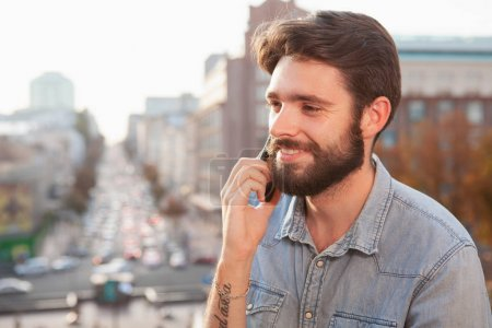 Photo for Close up of a handsome bearded young man smiling, talking on the phone outdoors in the city center, copy space. Connections, communication concept - Royalty Free Image