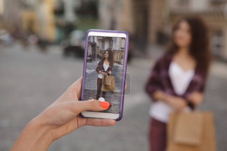 Photo for Cropped close up of a woman using smart phone, taking photos of her female friend in the city. Female friends wandering on city streets, taking photos with mobile phone - Royalty Free Image