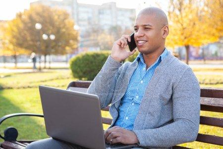 Photo pour Un homme à la pige qui parle au téléphone tout en travaillant à l'extérieur sur son ordinateur portatif. Beau jeune homme d'affaires afro-américain travaillant à l'extérieur dans le parc - image libre de droit
