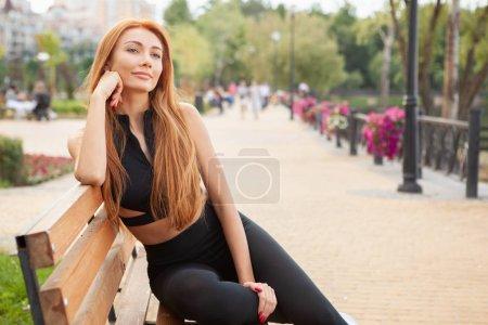 Photo pour Magnifique femme sportive regardant loin joyeusement, se reposant après l'entraînement en plein air, copier l'espace. Athlète féminine charmante se détendre à l'extérieur après l'exercice - image libre de droit