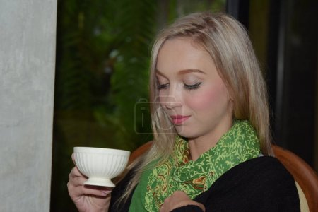 Photo for Beautiful girl is drinking coffee at the coffee shop. - Royalty Free Image