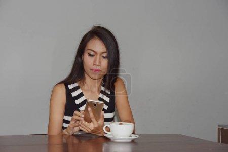 Photo pour La femme asiatique utilise le téléphone portable et le café potable - image libre de droit