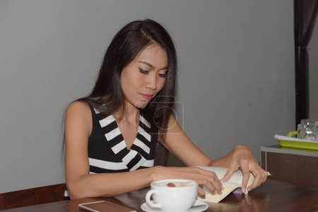 Photo for Asian woman is reading book and drinking coffee - Royalty Free Image