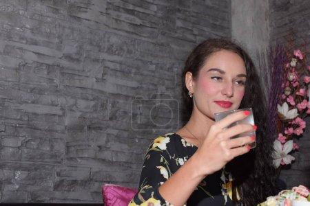 Photo pour La femme boit de l'eau dans le café - image libre de droit