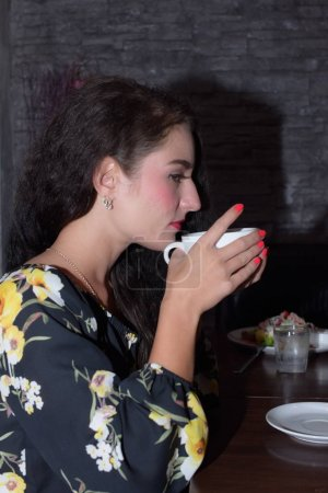 Photo for Beautiful woman is drinking coffee in cafe - Royalty Free Image