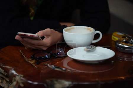 Photo for Woman is using mobile phone and drinking coffee - Royalty Free Image