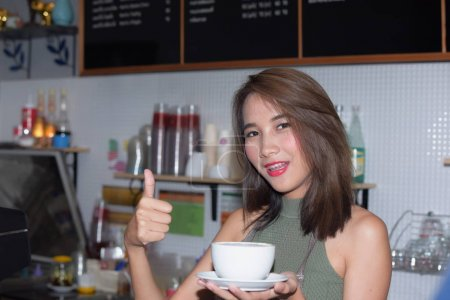 Photo for Woman holding cup with coffe and showing Ok sign - Royalty Free Image