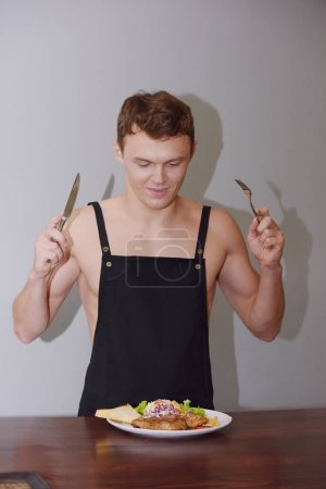 Photo for Caucasian man is holding fork with knife and preparing to eating food - Royalty Free Image
