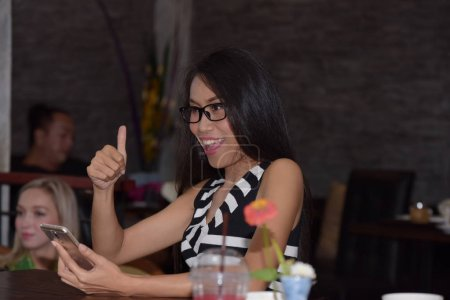 Photo for Asian woman using smartphone and showing Ok sign - Royalty Free Image