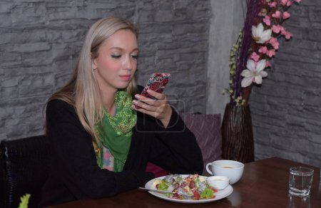Photo for The beautiful girl is using a mobile phone and eating at the restaurant. - Royalty Free Image