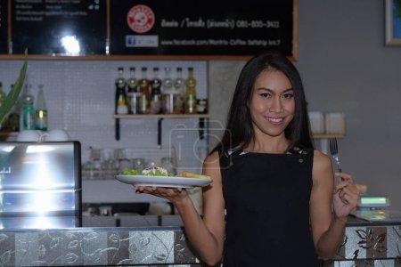 Foto de Hermosa mujer asiática sosteniendo plato en plato - Imagen libre de derechos
