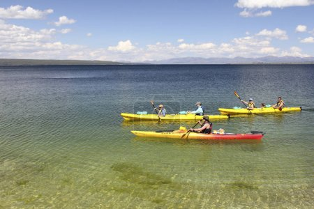 Tourists in kayaks paddle in the West Thumb Geyser Basin, on the shore of Lake Yellowstone.