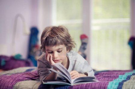 Cute little boy lying on bed reading book