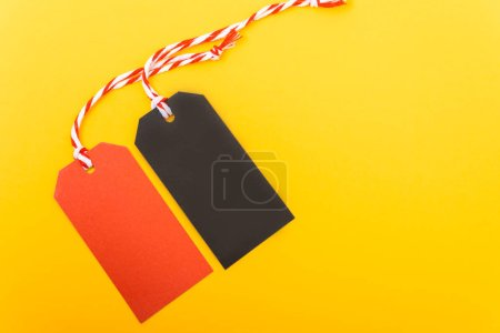 Photo for Red tag label and Black tag label on yellow background, blank copy space for you work - Royalty Free Image