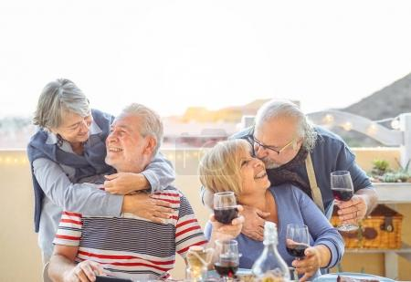Happy senior friends having fun  drinking red wine in terrace outdoor - Older people enjoying dinner and laughing together - Friendship and elderly lifestyle concept