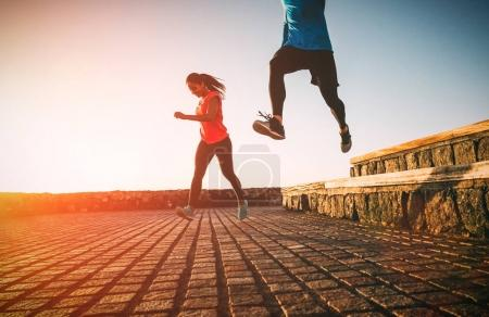 Health fit young couple running together during a magnificent sunset - Athletic friends doing sport outdoor - Sporty people training with jump exercises - Relationship, sport, lifestyle concept