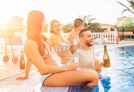Group of happy friends making a pool party at sunset - Young people laughing and having fun drinking champagne in vacation - Friendship, holidays, youth lifestyle concept